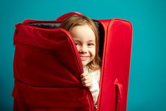 Little girl looks out of red suitcase on blue isolated background. stock photos