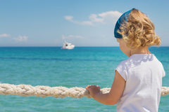 Little girl looks out to sea. Stock Photos