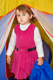 Little girl looks out of tourist tent Stock Photos