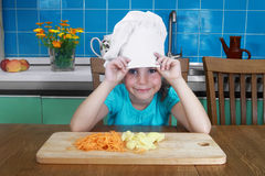 Little girl looks out from under chef hat Stock Photo
