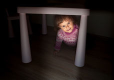 The little girl looks out from under the table. Royalty Free Stock Photos