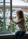 Little girl looks out the window. Royalty Free Stock Image