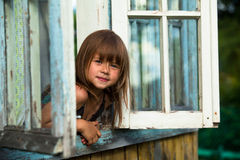 Little girl looks out the window rural house Royalty Free Stock Photography