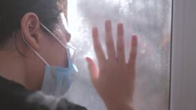 Little girl looks out the window sad in a medical gauze mask. concept pandemic virus self-isolation covid 19 infection