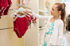 Little girl looks over closed swimsuit. In clothing store Royalty Free Stock Photos