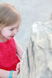 A little girl looks at a rock Stock Photo