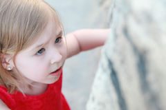 A little girl looks at a rock Stock Image