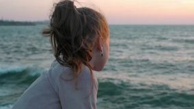 Little girl looks at the sea windy day at sunset. concept thought concentration lifestyle. Little girl looks at the sea windy day at sunset. concept thought and stock video footage