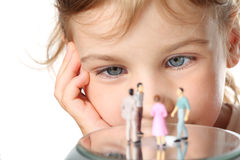 Little girl looks at small toy figures of people Royalty Free Stock Photo