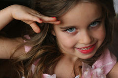 Little girl looks and smiles Stock Photos