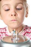 Little girl looks at toy figures of people Royalty Free Stock Images