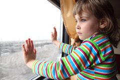 Little girl looks in train`s window Stock Images