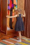 The little girl looks in the wardrobe. A nice little girl looks in the old wardrobe wardrobe. The concept of fashion, retro style, things of the fifties of last Stock Photos