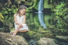 Little girl looks at the water sitting next to the bed of a rive Royalty Free Stock Photography