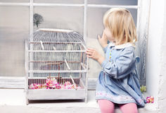 The little girl looks at the window. Little girl sitting on the windowsill next to a beautiful white cage and looks out the window Royalty Free Stock Photography