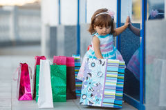 Little girl and lots of colorful bags Stock Photo