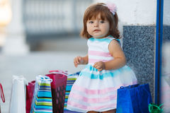 Little girl and lots of colorful bags Stock Photos