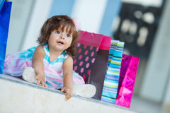Little girl and lots of colorful bags Royalty Free Stock Image