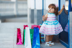 Little girl and lots of colorful bags Stock Images