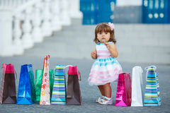 Little girl and lots of colorful bags Royalty Free Stock Images