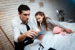 Little girl with lovely tails is interested in her father`s work. Buisnessman with daughter. royalty free stock image