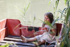 The little girl loves to spend time on the river. Little cute little girl sits in a boat on a lake and holds an apple in her hand. She enjoys a beautiful and Stock Photo