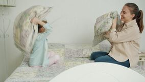 Little girl and loving mother are fighting pillows laughing relaxing in bed at home together