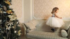 Little girl in the lush dress jumping on the couch stock video footage