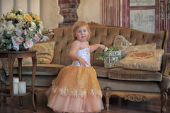 Little girl in the lush yellow with white dress Royalty Free Stock Images