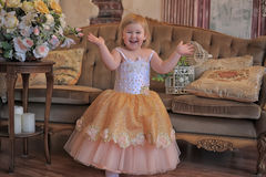 Little girl in the lush yellow with white dress. In the elegant interior Stock Photos