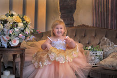 Little girl in the lush yellow with white dress. In the elegant interior Royalty Free Stock Photo
