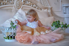 Little girl in the lush yellow with white dress. In the elegant interior Royalty Free Stock Images