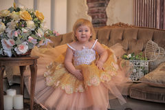 Little girl in the lush yellow with white dress. In the elegant interior Royalty Free Stock Photos