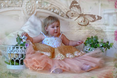 Little girl in the lush yellow with white dress. In the elegant interior Royalty Free Stock Image