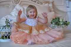 Little girl in the lush yellow with white dress. In the elegant interior Stock Photo