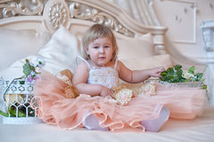 Little girl in the lush yellow with white dress. In the elegant interior Stock Image