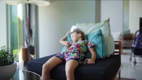 Little girl is lying on the armchair near the panoramic window and is bored, slow motion. Little girl is lying on the armchair near the panoramic window and is stock video footage
