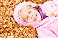 Little Girl Lying in Autumn Leaves Royalty Free Stock Photography