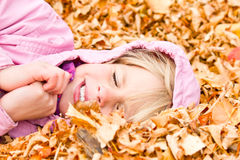 Little Girl Lying in Autumn Leaves Royalty Free Stock Photo