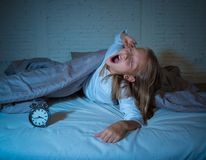 Little girl lying awake in the middle of the night tired and restless suffering sleeping disorders. Cute sleepless little girl lying in bed looking sad and tired royalty free stock image