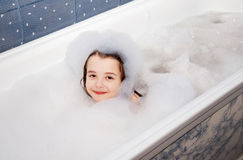 Little girl lying in a bath with soap suds. Closeup Stock Photography
