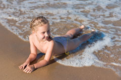 Little girl lying on the beach Royalty Free Stock Image