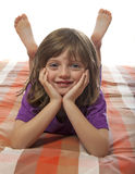 Little girl lying on a bed Stock Images