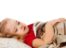 Little girl lying in bed. With a thermometer Stock Image