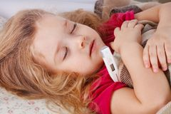 Little girl lying in bed. With a thermometer Stock Photography