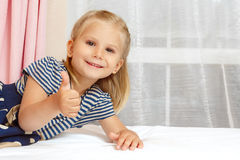 Little girl lying on the bed stock image