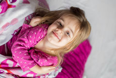 Little girl lying on the bed Stock Photography