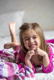 Little girl lying on the bed. With bare feet ,beautiful smiles,the concept of sleep and rest Royalty Free Stock Photos
