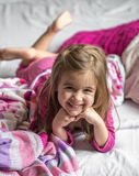 Little girl lying on the bed. With bare feet ,beautiful smiles,the concept of sleep and rest Royalty Free Stock Photography