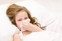 Little girl lying in the bed blowing her nose Royalty Free Stock Photography